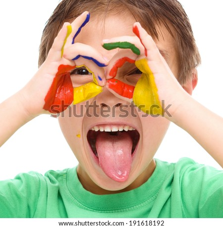 Portrait of a cute cheerful boy showing his hands painted in bright colors and sticking tongue out, isolated over white - stock photo