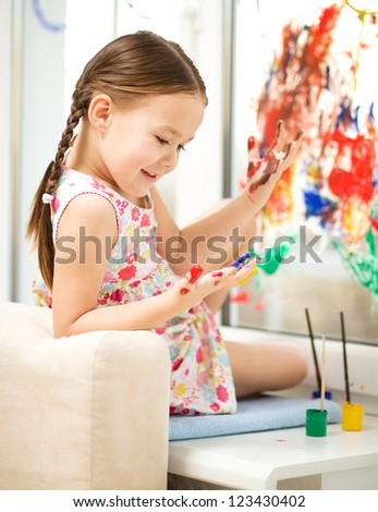 Portrait of a cute cheerful girl playing with paints on window - stock photo