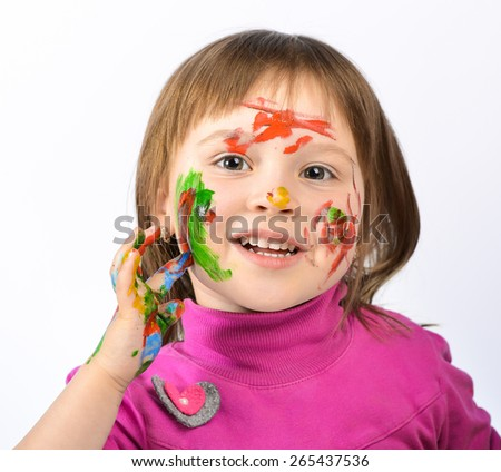 Portrait of a cute cheerful girl showing her hands painted in bright colors, on a white background