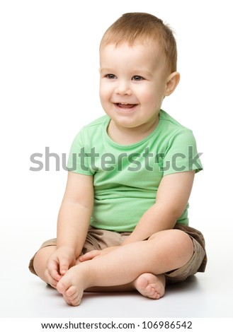 Portrait of a cute cheerful little boy, who is smiling while sitting on floor, isolated over white