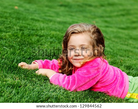 Portrait of a cute cheerful preschool girl in park - stock photo