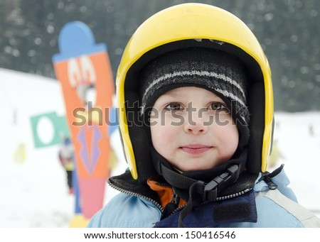 Portrait of a cute child skier, boy or girl, with yellow skiing helmet in a winter ski resort. - stock photo