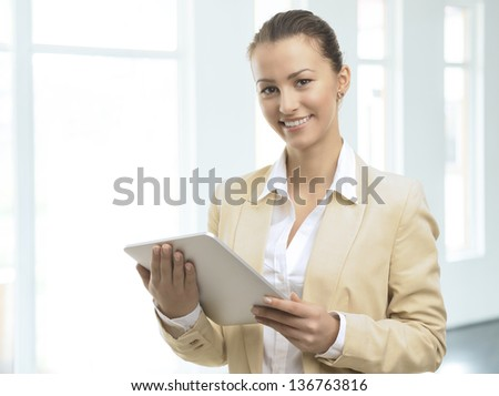 Portrait of a cute confident business woman with digital tablet in office - stock photo