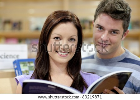 Portrait of a cute couple reading a book in a shop and smiling at the camera - stock photo