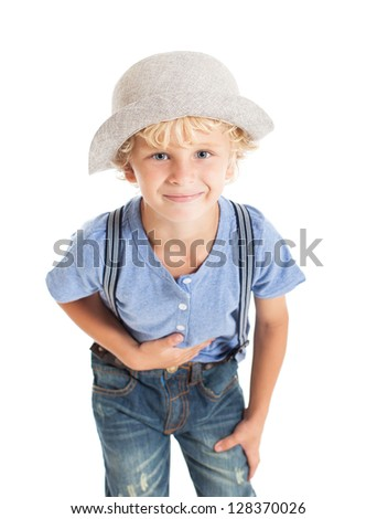 Portrait of a cute curly blond boy wearing a blue shirt, suspenders and hat. The boy bowed, his hand on his chest and smiled. Studio shot, isolated on white background. - stock photo