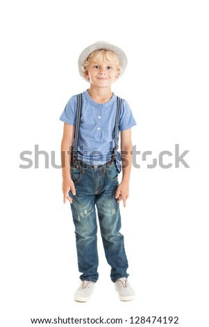 Portrait of a cute curly blond boy wearing a blue shirt, suspenders, jeans and a hat in full growth. Studio shot, isolated on white background. - stock photo