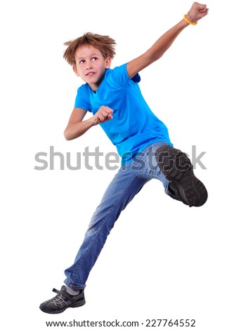Portrait of a cute elementary boy jumping and dancing.  Isolated over white background - stock photo