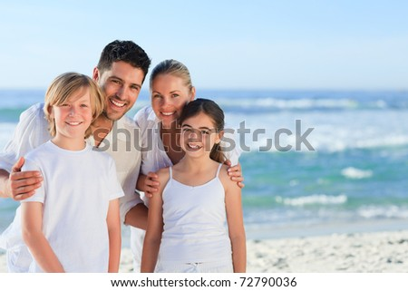 Portrait of a cute family at the beach - stock photo