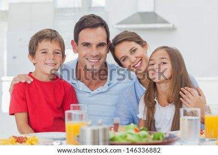 Portrait of a cute family at the table - stock photo