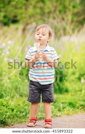 Portrait of a cute funny little boy toddler standing in the forest field meadow with dandelion flowers in hands and blowing them on a bright summer day, summer fun, copyspace for text - stock photo
