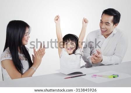 Portrait of a cute girl expressing happy after finishing her homework with her parents and get applause, isolated on white background - stock photo