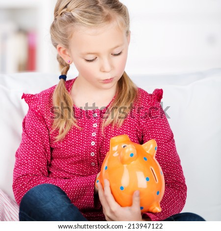portrait of a cute girl looking at piggy bank - stock photo