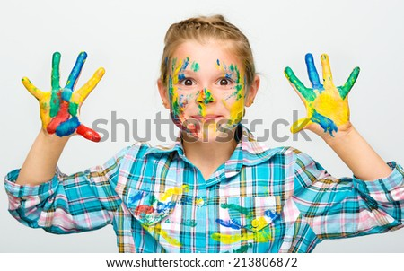 Portrait of a cute girl showing her hands painted in bright colors - stock photo