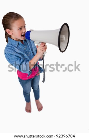 Portrait of a cute girl speaking through a megaphone against a white background - stock photo