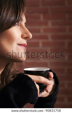 portrait of a cute girl with cup at wall - stock photo