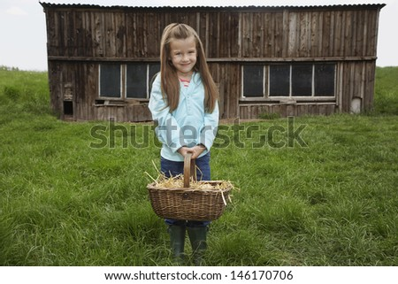 Portrait of a cute girl with egg basket on grassland with farmhouse in background