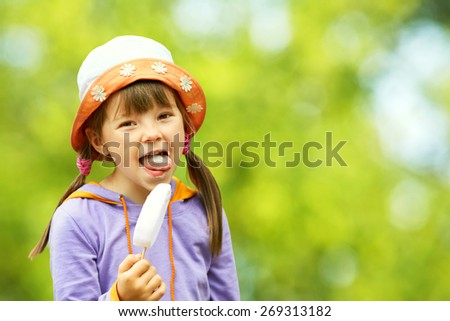 Portrait of a cute girl with ice cream on a walk in the park. child outdoors - stock photo