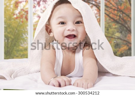 Portrait of a cute little baby boy laughing on the bed under a towel and look at the camera - stock photo