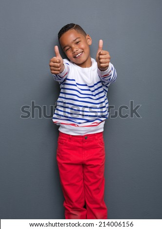 Portrait of a cute little black boy smiling with thumbs up sign on gray background - stock photo