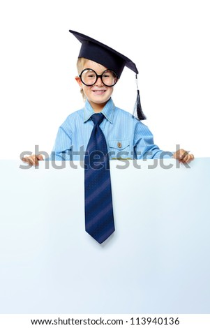Portrait of a cute little boy in academic hat and big spectacles holding white board. Isolated over white background. - stock photo
