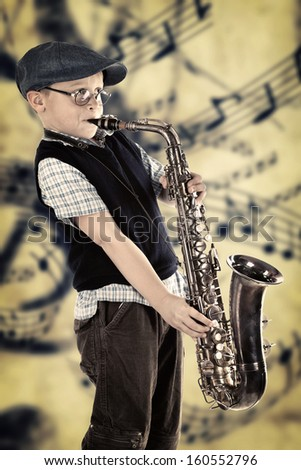 Portrait of a cute little boy jazz man playing his saxophone. Retro style with old Music background  - stock photo