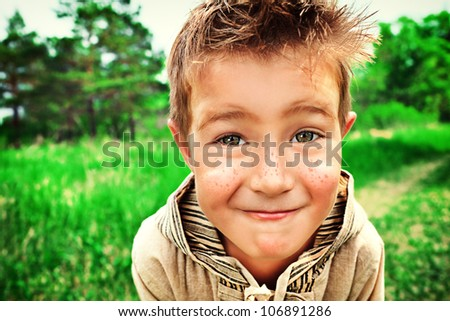 Portrait of a cute little boy playing outdoor. - stock photo
