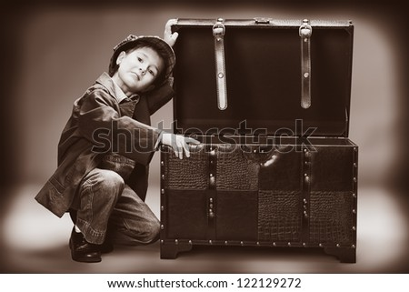 Portrait of a cute little boy sitting with a huge old trunk. Vintage style. - stock photo
