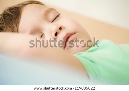 Portrait of a cute little boy sleeping in bed - stock photo