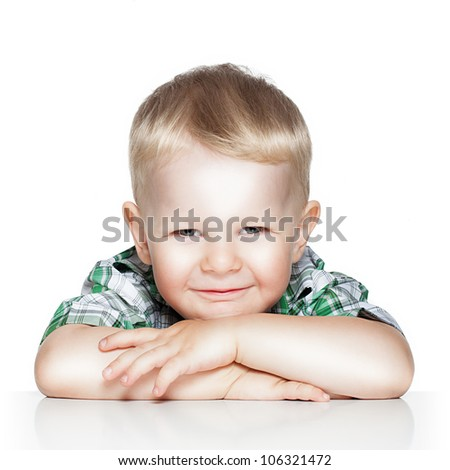 Portrait of a cute little boy smiling while sitting at table, isolated over white - stock photo
