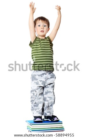Portrait of a cute little boy standing on books. Isolated over white background. - stock photo