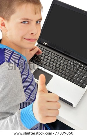 Portrait of a cute little boy using a laptop thumbs up and smiling - Indoor - stock photo