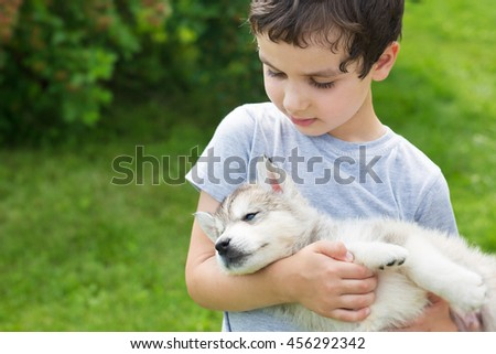 Portrait of a cute little boy with a sleeping husky puppy - stock photo