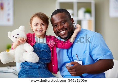 Portrait of a cute little girl and her doctor at hospital - stock photo
