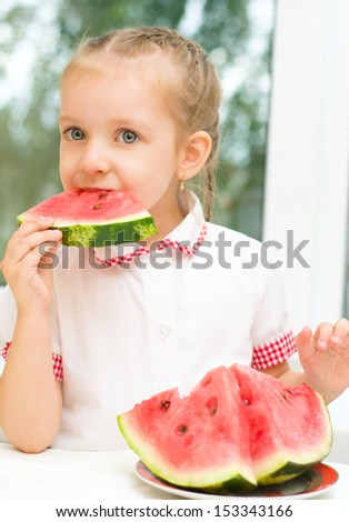 portrait of a cute little girl eating watermelon