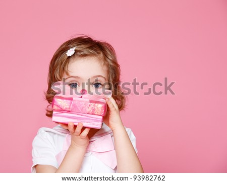 Portrait of a cute little girl hiding face behind pink present box - stock photo