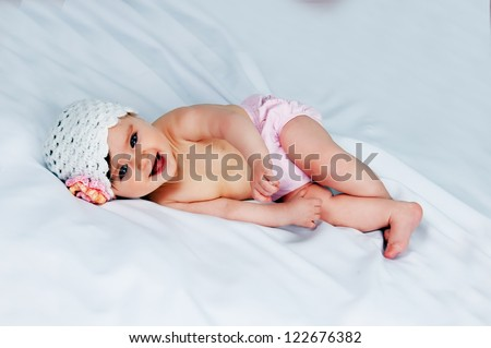 Portrait of a cute little girl in a cap on a white background