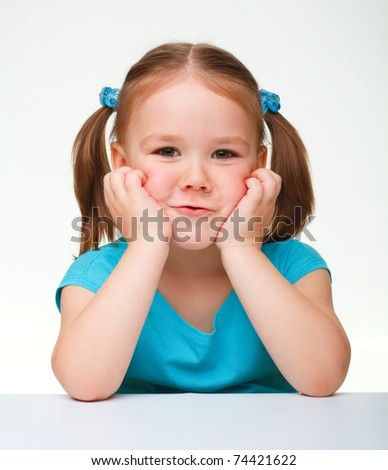 Portrait of a cute little girl making funny face, isolated over white - stock photo