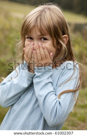Portrait of a cute little girl nine years old closing to her mouse by her hands - stock photo