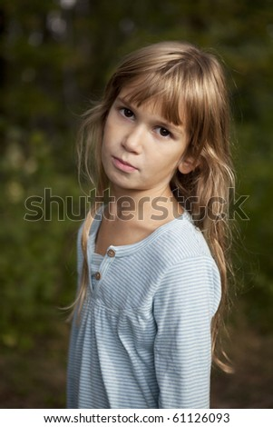Portrait of a cute little girl nine years old closing to her mouse by her hands