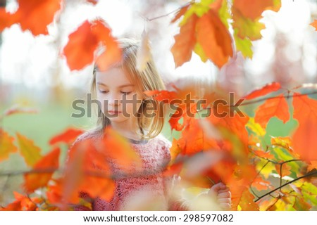 Portrait of a cute little girl on beautiful golden autumn day