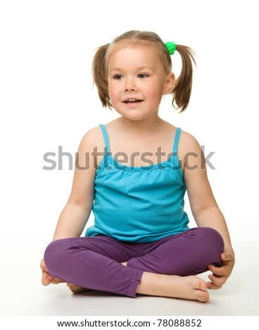 Portrait of a cute little girl sitting on floor, isolated over white - stock photo