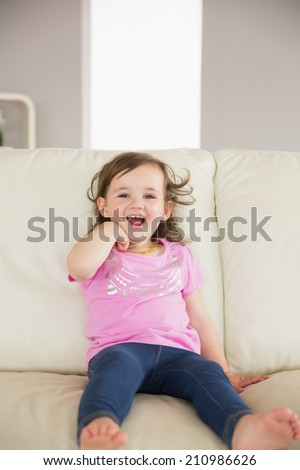 Portrait of a cute little girl sitting on sofa at home - stock photo