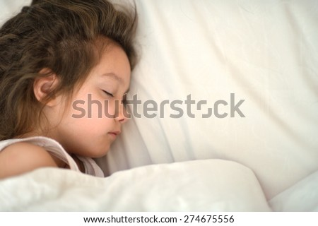 Portrait of a cute little girl sleeping in bed - stock photo