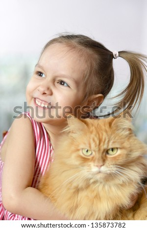 portrait of a cute little girl with a red cat at home