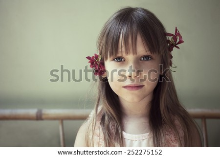 Portrait of a cute little girl with long hair and flowers in her hair - stock photo