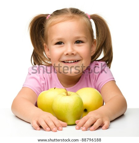 Portrait of a cute little girl with three yellow apples, isolated over white - stock photo