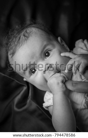 Portrait of a cute little mixed race baby sucking on her mom's index finger