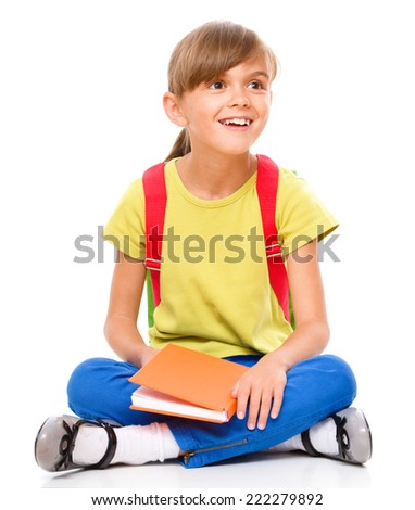 Portrait of a cute little schoolgirl with backpack reading her book, isolated over white - stock photo