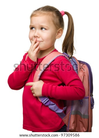 Portrait of a cute little schoolgirl with backpack thinking about something, isolated over white - stock photo