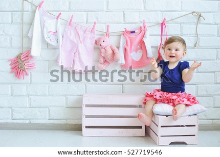 Portrait of a cute little smiling girl with baby clothes hanging on background